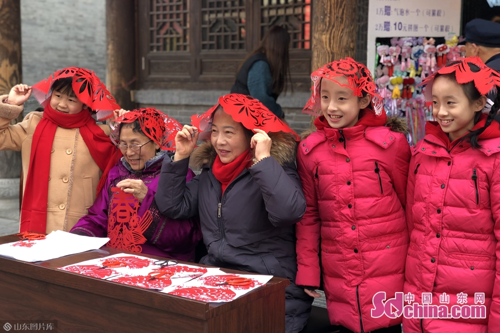 Folk artists and visitors pose for a photo in Qingzhou Ancient Town Scenic Spot in Weifang City, east China&rsquo;s Shandong Province. A series of events will be held here to greet the Chinese Lunar New Year, or Spring Festival, which falls on Feb. 5 this year.<br/>