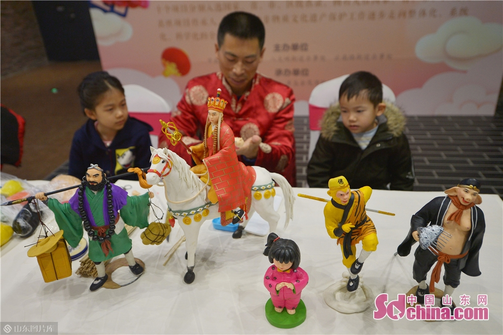 A craftsman displays the dough modeling in Xizhen Museum of Qingdao, east China&amp;rsquo;s Shandong Province on January 28, 2019. The Intangible Cultural Heritage Exhibition kicked off here on Monday to greet the Chinese Lunar New Year, which falls on Feb. 5 this year.<br/>