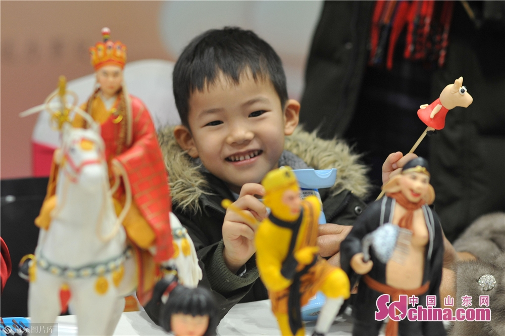 A child plays with the dough figures in Xizhen Museum of Qingdao, east China&amp;rsquo;s Shandong Province on January 28, 2019. The Intangible Cultural Heritage Exhibition kicked off here on Monday to greet the Chinese Lunar New Year, which falls on Feb. 5 this year.<br/>