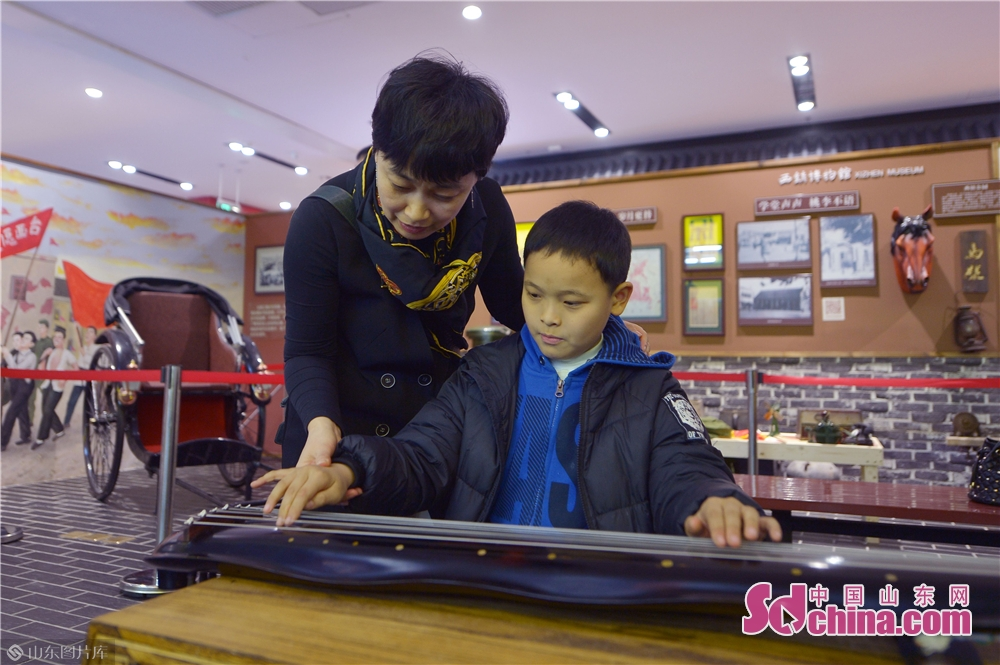 A child plays the Chinese zither in Xizhen Museum of Qingdao, east China&amp;rsquo;s Shandong Province on January 28, 2019. The Intangible Cultural Heritage Exhibition kicked off here on Monday to greet the Chinese Lunar New Year, which falls on Feb. 5 this year.<br/>