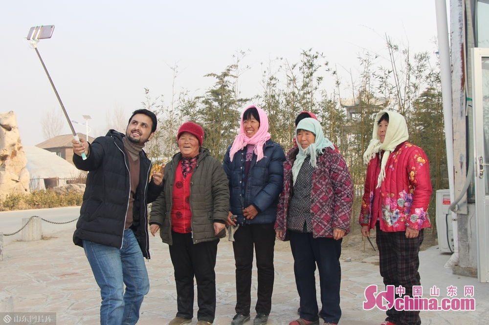 Foreigners take photos with farmers in Huiquan Agro-ecological Park in Zhangqiu District of Jinan, capital of Shandong Province, on January 3, 2019. More than 10 foreign students at Shandong University arrived in Zhangqiu Huiquan Agro-ecological Park to gain intuitive insights into the development of modern agriculture and agricultural tourism in Shandong.<br/>