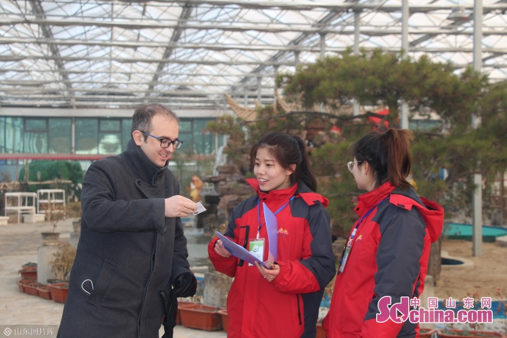 A foreigner chats with staff members of Huiquan Agro-ecological Park in Zhangqiu District of Jinan, capital of Shandong Province, on January 3, 2019. More than 10 foreign students at Shandong University arrived in Zhangqiu Huiquan Agro-ecological Park to gain intuitive insights into the development of modern agriculture and agricultural tourism in Shandong.<br/>