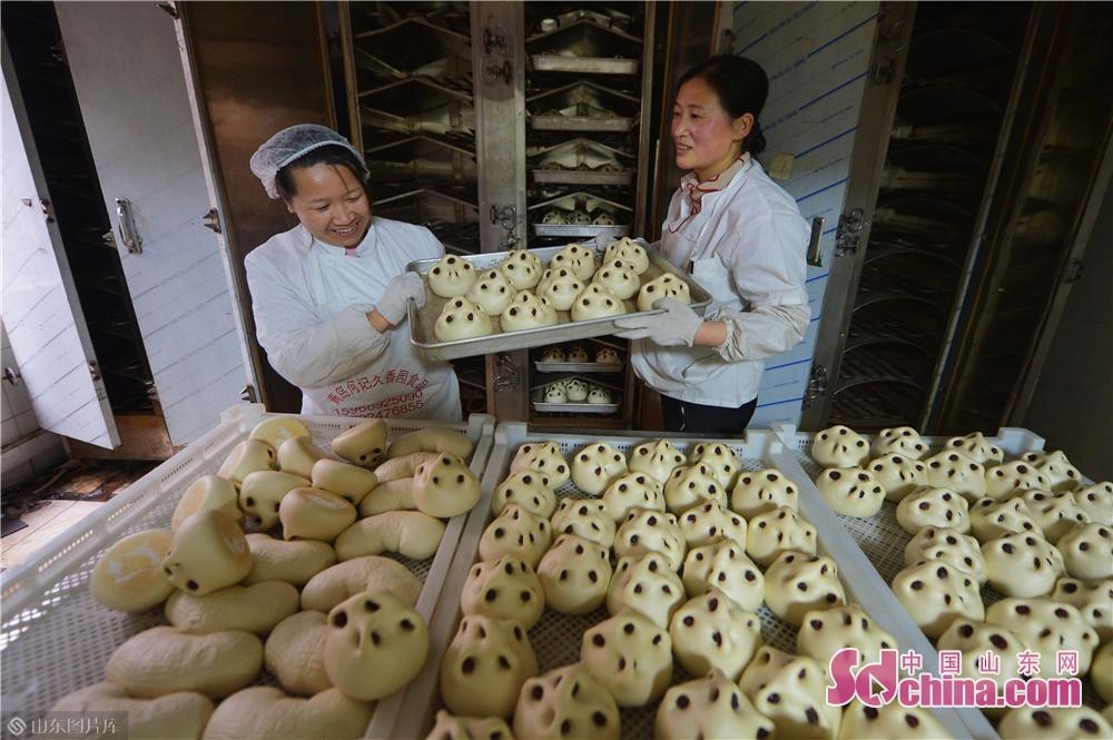 <br/> <br/>  2019年1月30日,面食师傅在青岛崂山区王哥庄荆长艳的馒头店里从烤箱取出枣馒头。<br/>