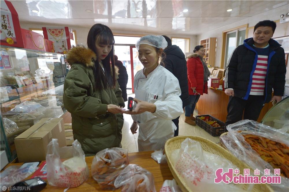 <br/> <br/>  2019年1月30日,一名市民在青岛崂山区王哥庄荆长艳的馒头店里用手机支付馒头款。<br/>