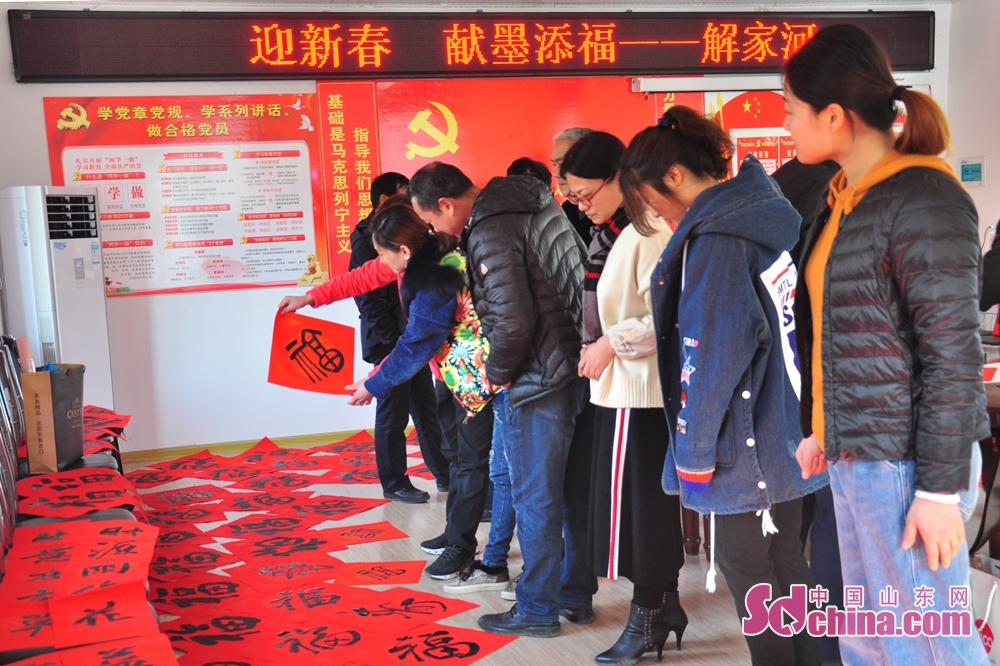 Calligraphers prapare calligraphy works to hand out to residents to celebrate the upcoming Spring Festival, or Chinese Lunar New Year, in Xiejiahe Community of Wanggezhuang Street in Qingdao, east China's Shandong Province on January 31, 2019.
