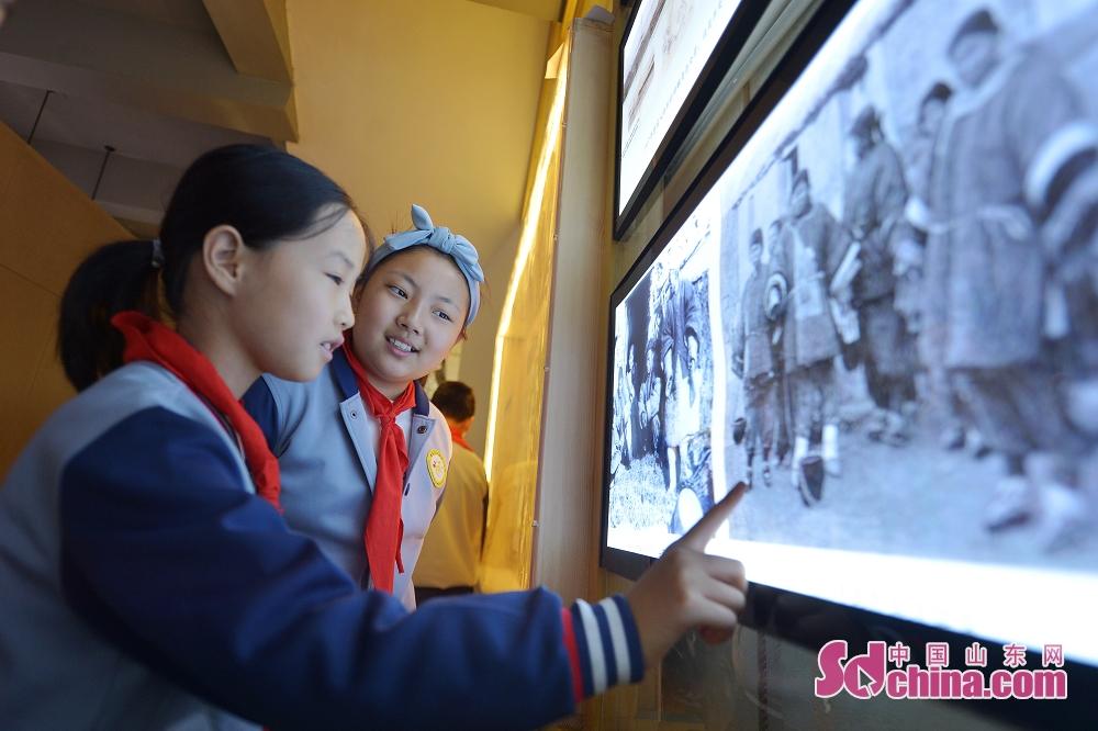 <br/>  10月9日,两名青岛北仲一路小学的学生在青岛历史街区文化记忆馆观看清末居民老照片。<br/>