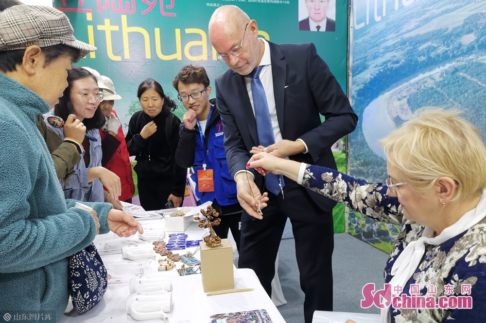 Lithuanian exhibitors show visitors the amber fashion accessories at the Jinan International Sister Cities Commodity Expo in Jinan, East China&rsquo;s Shandong Province, Oct. 15, 2019. The expo kicked off here on Tuesday.<br/>