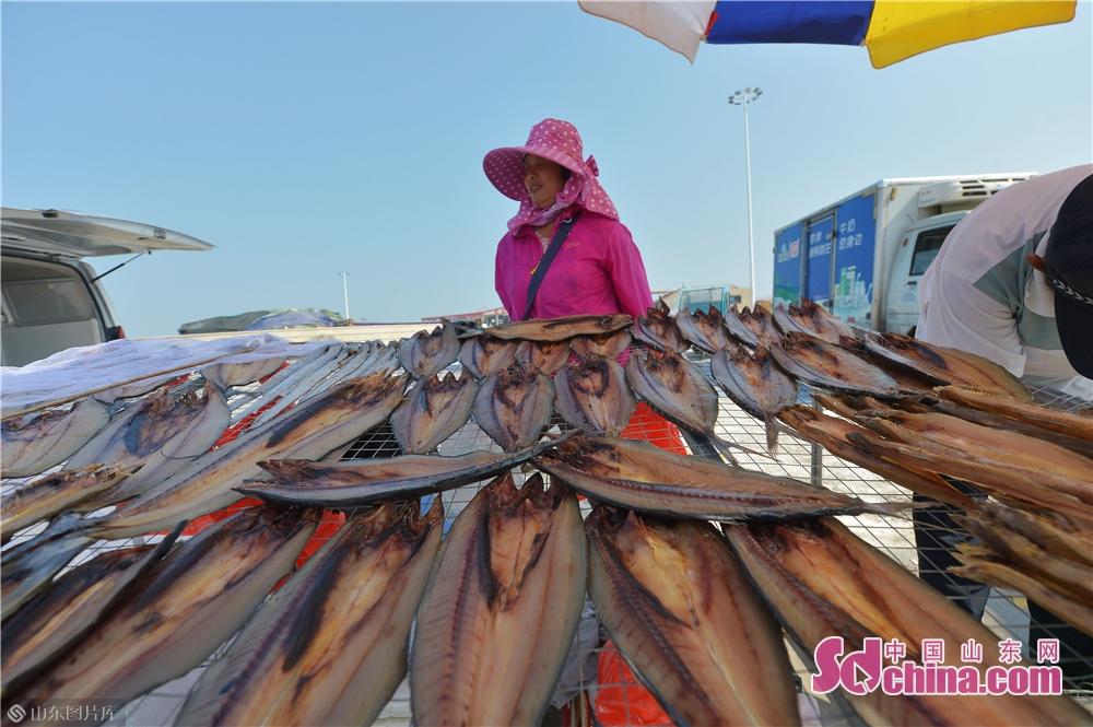 <br/>  2019年10月3日,渔民在青岛崂山区港东码头向顾客展示新近腌制的鲅鱼干。<br/>