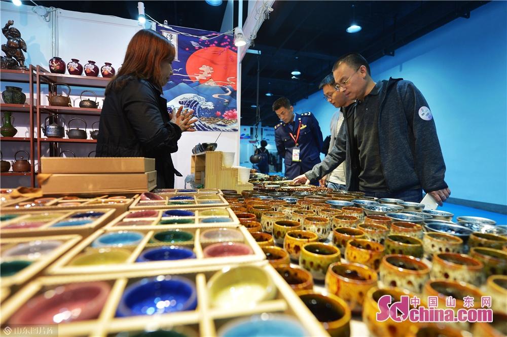 来場者は日本・韓国(青島)輸入商品博覧会で日本の茶道具を買った。