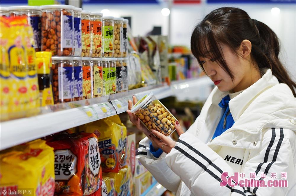 2019년 11월 15일, 고객은 일한(청도) 수입상품박람회 침천 혁신제품관에서 한국 과자를 골라서 구매하고 있다.<br/>