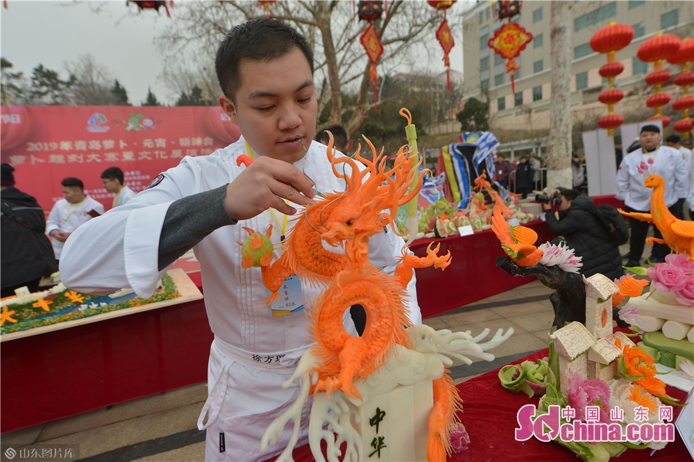 An artist works on food carving during the Qingdao Radish &amp; Sweet Dumplings &amp; Tomatoes on Sticks Festival in Qingdao, east China&amp;rsquo;s Shandong Province on Feb. 13, 2019.<br/>