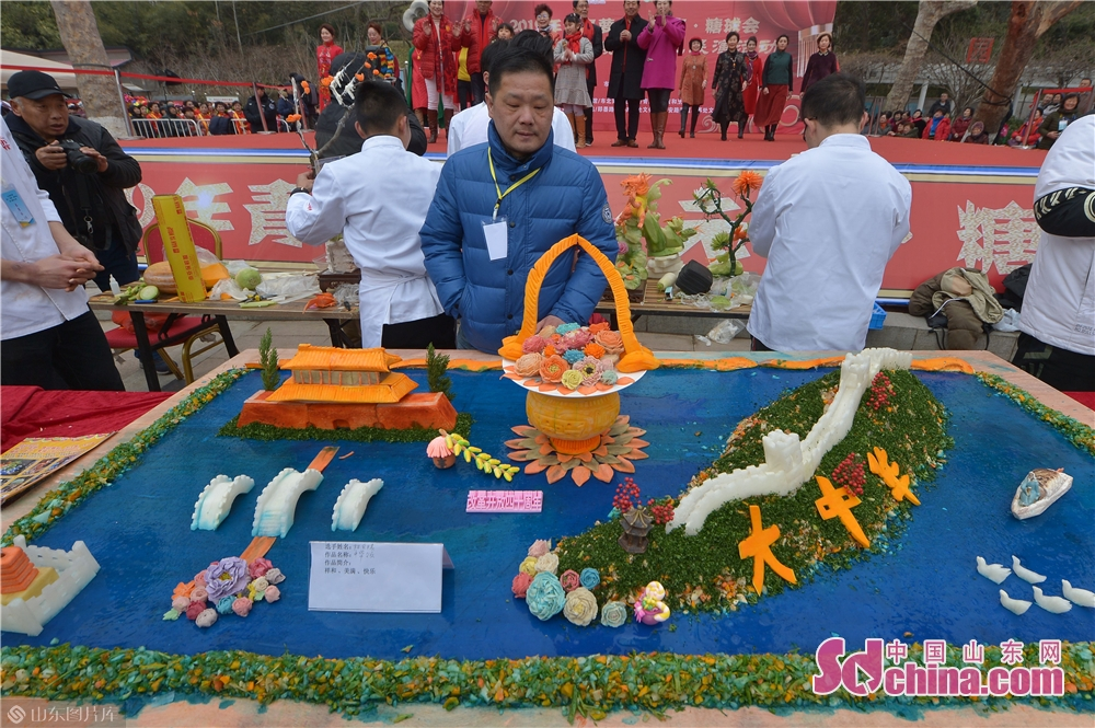 A judge looks at a piece of food carving work during the Qingdao Radish & Sweet Dumplings & Tomatoes on Sticks Festival in Qingdao, east China's Shandong Province on Feb. 13, 2019.