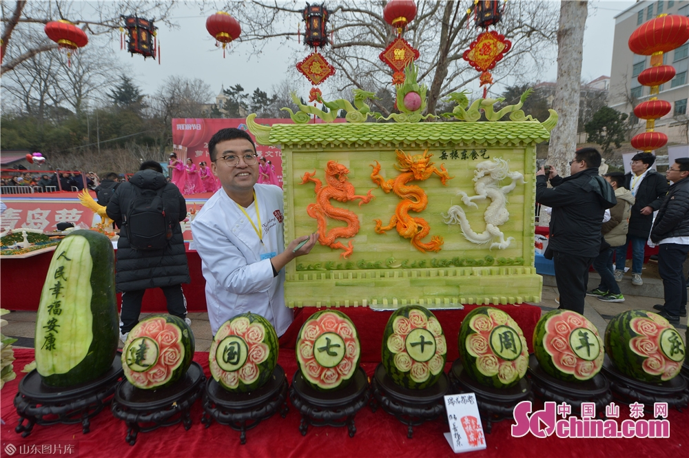 An artist presents his food carving work during the Qingdao Radish &amp; Sweet Dumplings &amp; Tomatoes on Sticks Festival in Qingdao, east China&amp;rsquo;s Shandong Province on Feb. 13, 2019.<br/>