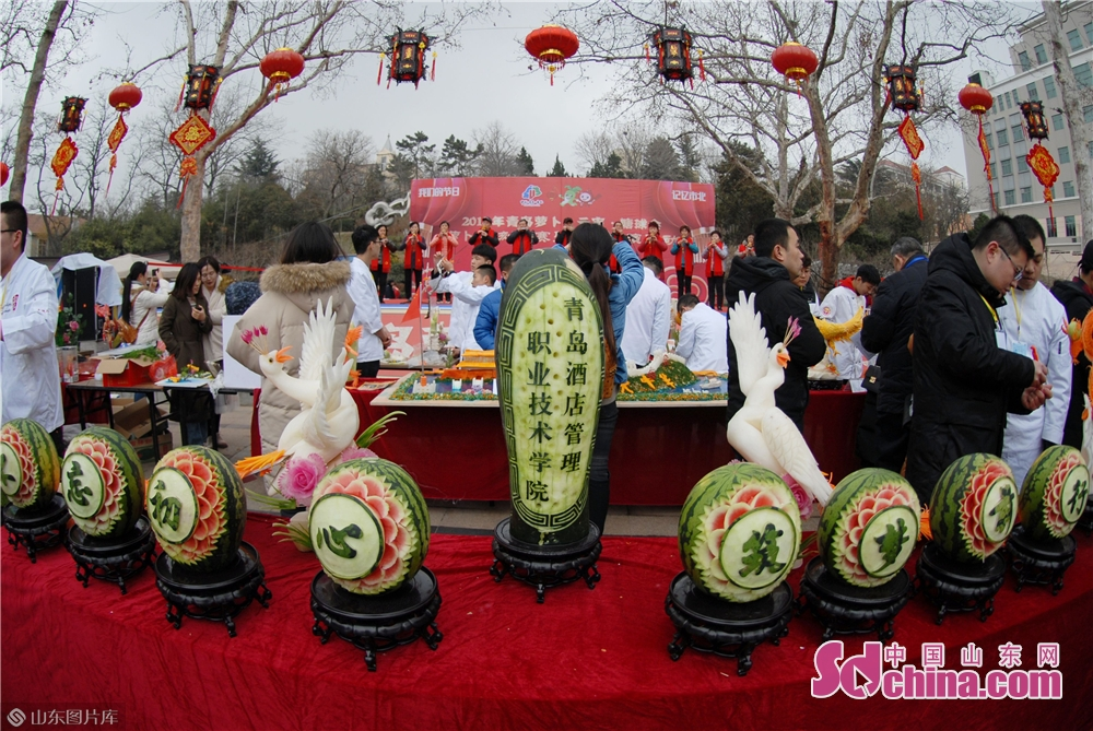 Visitors look at food carving works during the Qingdao Radish &amp; Sweet Dumplings &amp; Tomatoes on Sticks Festival in Qingdao, east China&amp;rsquo;s Shandong Province on Feb. 13, 2019.<br/>