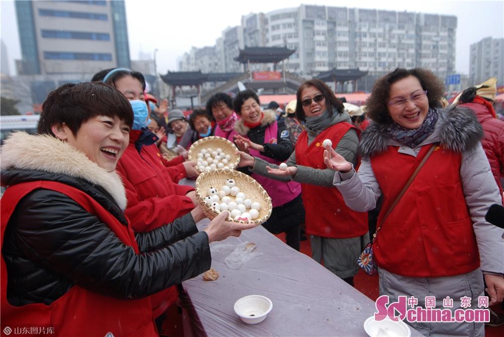2月19日,市民展示在山东青岛海云庵糖球会元宵制作大赛上包出的各式汤圆。