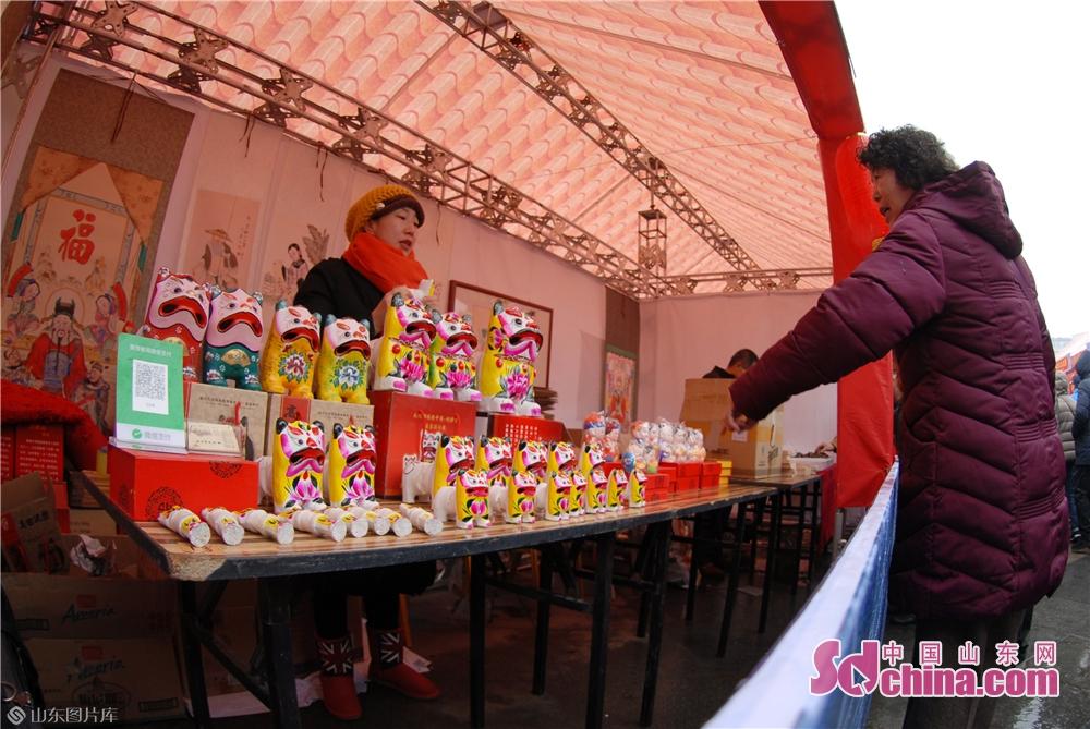 2月19日,游客在山东青岛海云庵糖球会观看高密泥老虎。<br/>