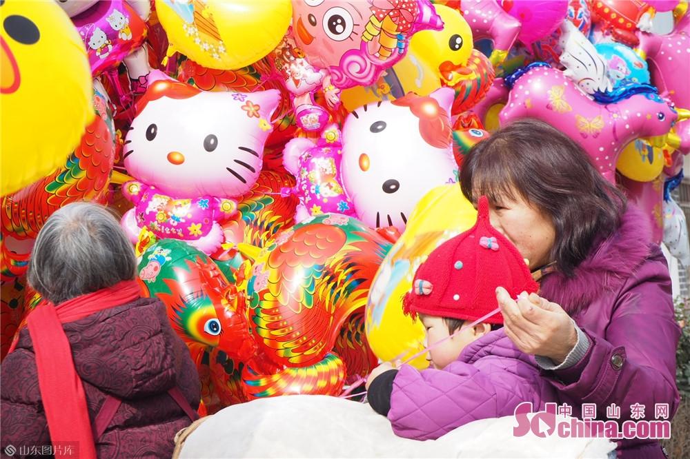 图为姜屯村集市上,一名小朋友得到了气球。2月4日,山东省临沂市临沭县郑山镇姜屯村的集市人头攒动,热闹非凡。当日正值农历腊月三十,在当地,每年的这一天被称为天下集,附近村民纷纷到集市上购买年货和生活必需品,迎接农历新年到来。<br/>