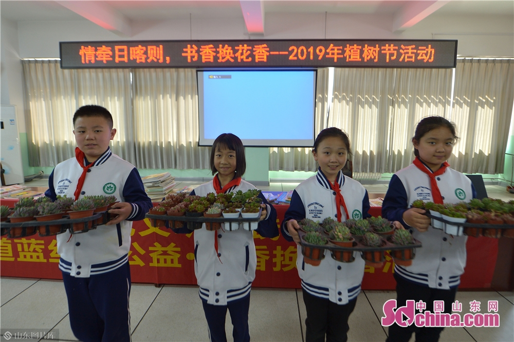 Students of Qingdao Lixin Primary School show green plants received during the &quot;books for flowers&quot; activity on the Arbor Day in Qingdao, a coastal city of Shandong province on March 12, 2019.<br/>