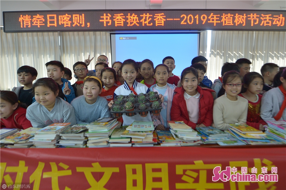 """Students of Qingdao Lixin Primary School show green plants received during the """"books for flowers"""" activity on the Arbor Day in Qingdao, a coastal city of Shandong province on March 12, 2019."""