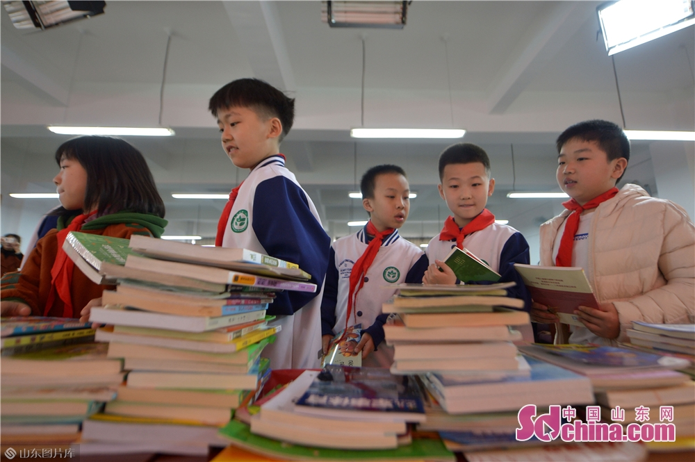 Students of Qingdao Lixin Primary School donate their extracurricular reading materials during the &quot;books for flowers&quot; activity on the Arbor Day in Qingdao, a coastal city of Shandong province on March 12, 2019.<br/>