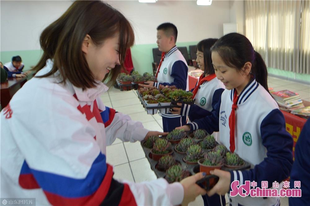 <br/>  8.3月12日,青岛双山街道工作人员在植树节&amp;ldquo;书香换花香&amp;rdquo;活动中向孩子们赠送绿植。<br/>