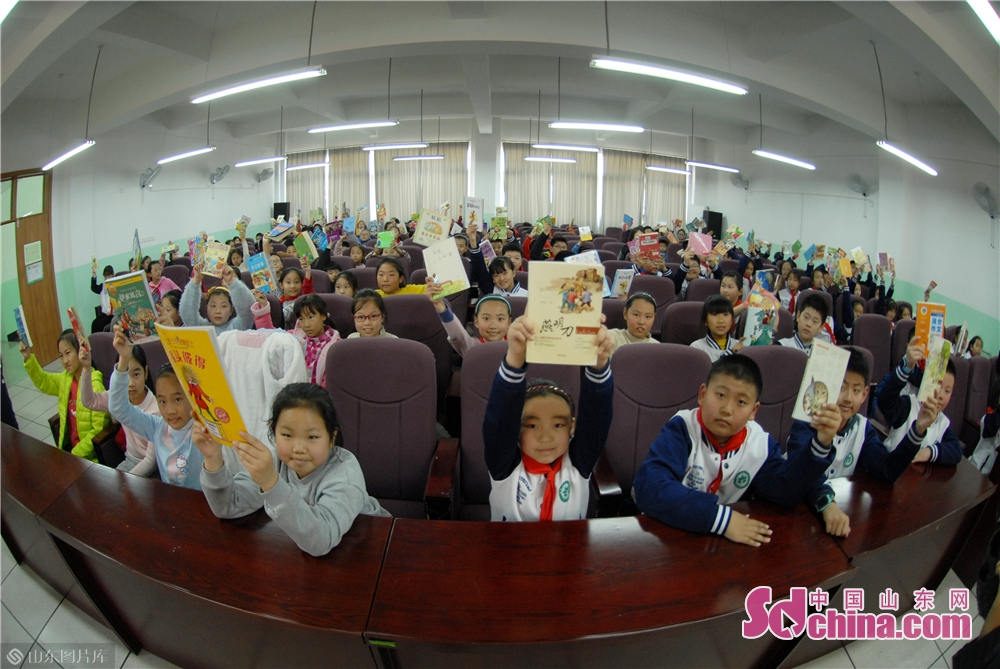 Students of Qingdao Lixin Primary School show the extracurricular reading materials for donation during the &quot;books for flowers&quot; activity on the Arbor Day in Qingdao, a coastal city of Shandong province on March 12, 2019.<br/>