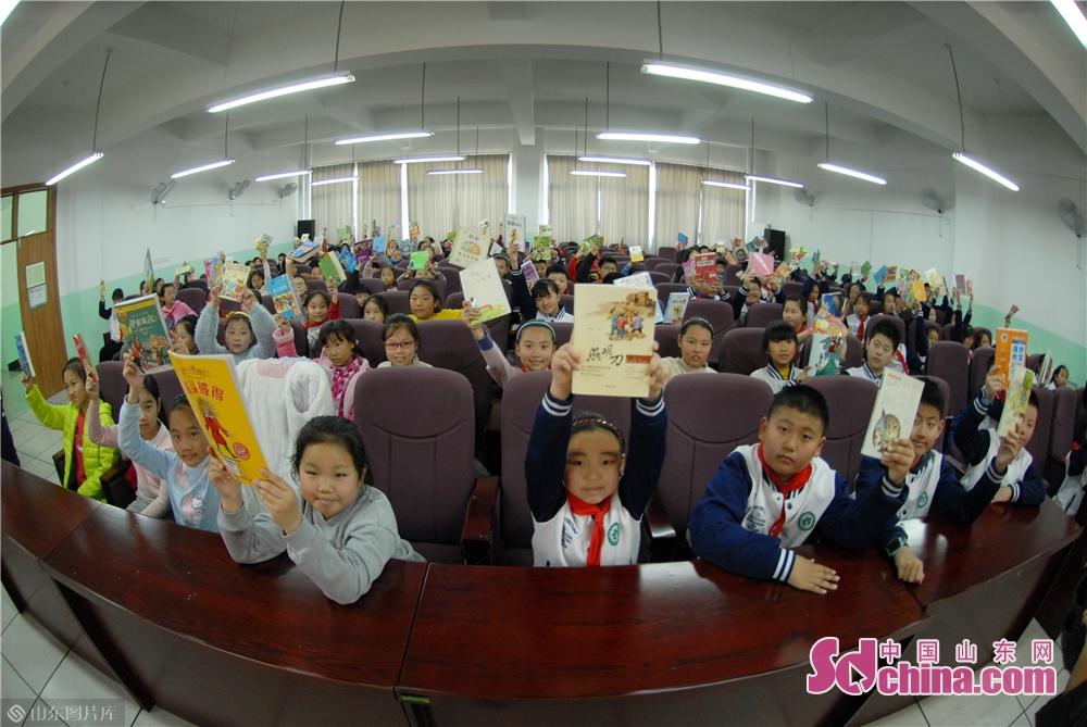 <br/>  3月12日,青岛立新小学的学生在植树节&amp;ldquo;书香换花香&amp;rdquo;活动中,展示准备捐赠的课外读物。<br/>