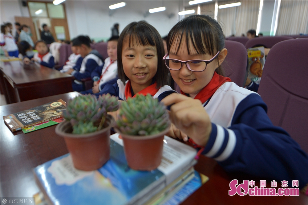 Two students of Qingdao Lixin Primary School show green plants received during the &quot;books for flowers&quot; activity on the Arbor Day in Qingdao, a coastal city of Shandong province on March 12, 2019.<br/>
