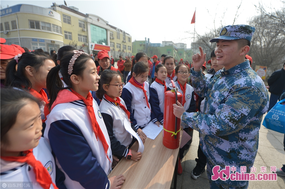 A soldier of the PLA navy explains fire-fighting knowledge to students in Qingdao, east China's Shandong province on March 4, 2019. A series of activities was held here on Monday to mark the Lei Feng Day.<br/>