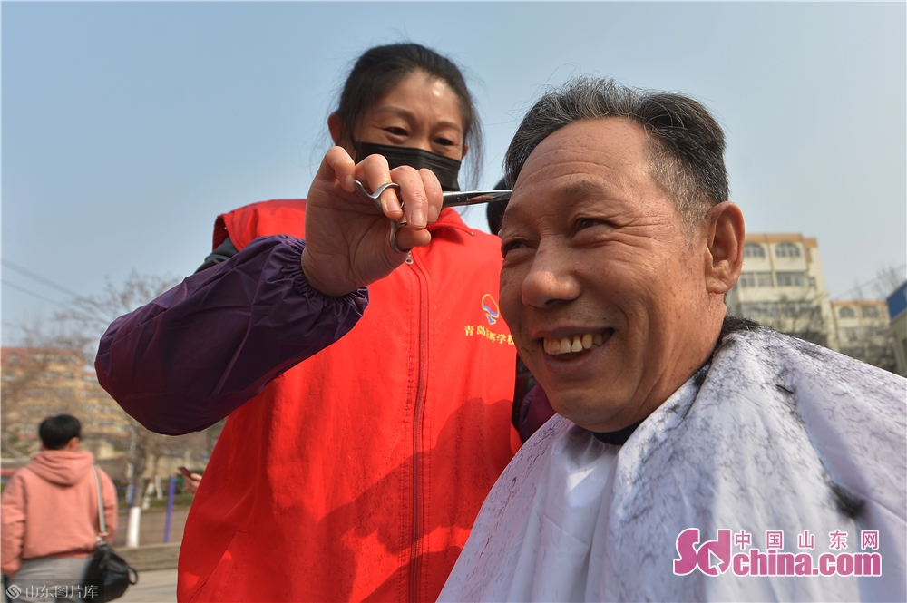 A volunteer cuts hair for a resident in Qingdao, east China's Shandong province on March 4, 2019. A series of activities was held here on Monday to mark the Lei Feng Day.<br/>