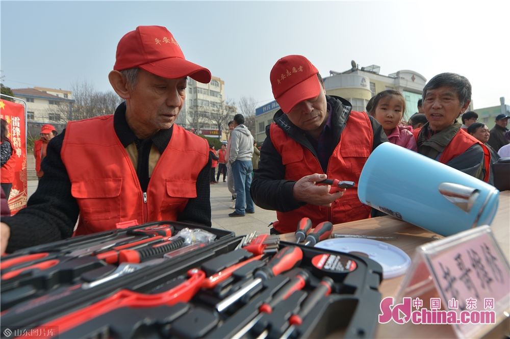 Volunteers repair electrical appliances for residents in Qingdao, east China's Shandong province on March 4, 2019. A series of activities was held here on Monday to mark the Lei Feng Day.<br/>