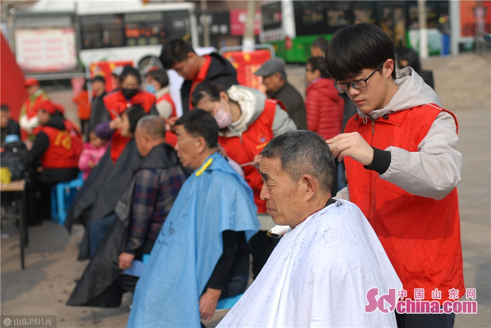 Volunteer cuts hair for residents in Qingdao, east China's Shandong province on March 4, 2019. A series of activities was held here on Monday to mark the Lei Feng Day.<br/>