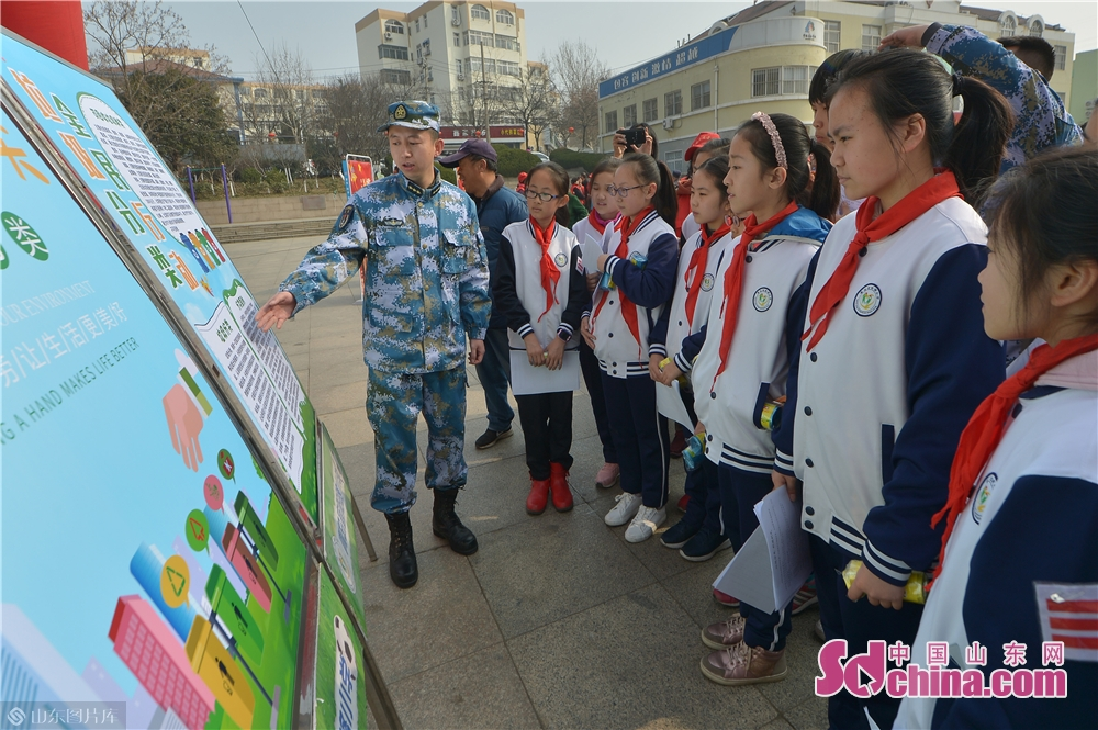A soldier of the PLA navy explains knowledge of garbage classification to students in Qingdao, east China's Shandong province on March 4, 2019. A series of activities was held here on Monday to mark the Lei Feng Day.<br/>