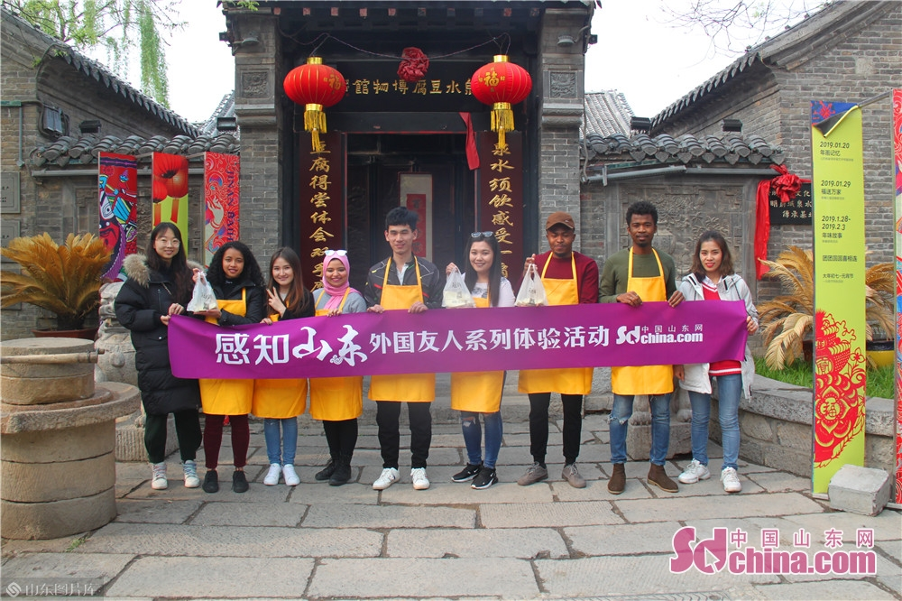 Foreigners pose for a group photo in Jinan Spring Tofu Museum in Jinan, capital of China's Shandong Province. Recently, six foreigners from Egypt, Mongolia, Madagascar and Nigeria went to Spring Tofu Museum in Baihuazhou Cultural and Historical Block in Jinan to experience the traditional method of making tofu.
