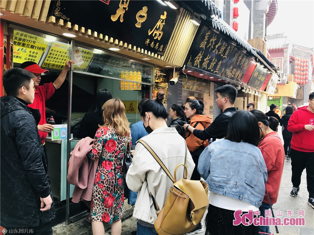 Tourists buy food in Furongjie Block in Jinan, capital of Shandong Province on April 3, 2019. As the weather gets warm in Jinan, the spring scenery of Furongjie-Baihuazhou Historical and Cultural Blocks has attracted tremendous tourists recently.<br/>
