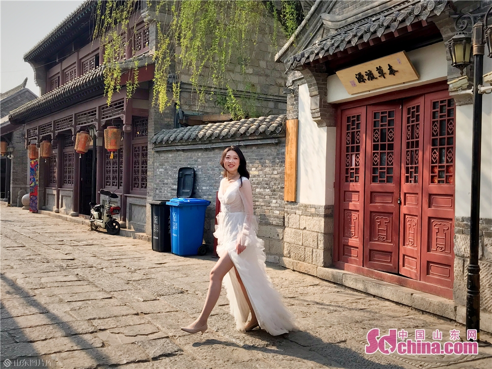 A woman poses for wedding pictures in Baihuazhou Block in Jinan, capital of Shandong Province on April 3, 2019. As the weather gets warm in Jinan, the spring scenery of Furongjie-Baihuazhou Historical and Cultural Blocks has attracted tremendous tourists recently.<br/>