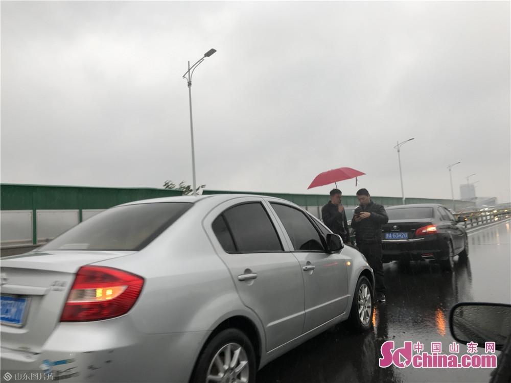 道路湿滑容易发生交通事故,提醒大家注意保持车距慢行。今日,在二环东路高架桥上,两辆小轿车发生了剐蹭,不仅在雨中处理事故不便,还增加了拥堵。<br/>