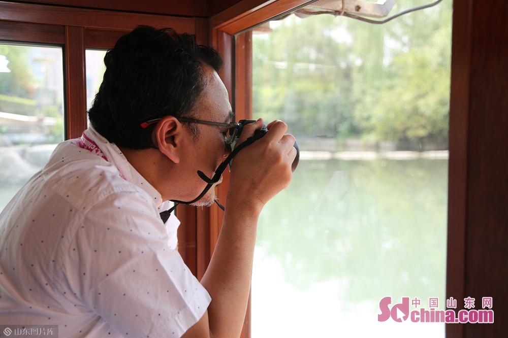 <br/>  船外景色秀美,外媒记者纷纷拍照。<br/>