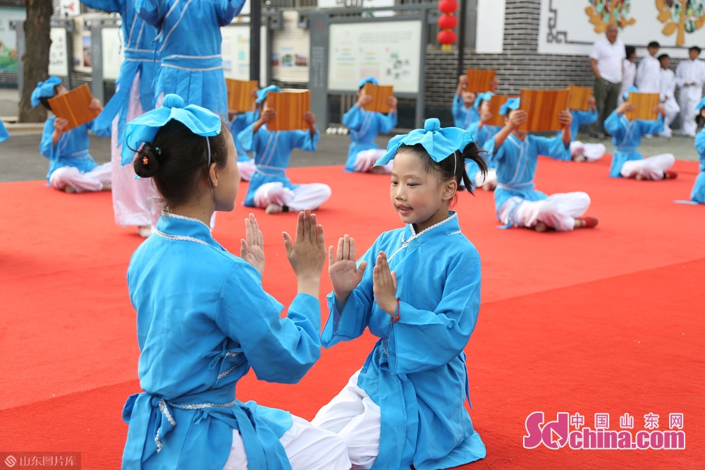 Children of the village perform in traditional Chinese costumes on the culture square.<br/>