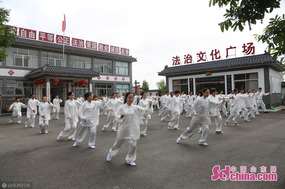 Villagers practice tai chi on the culture square.<br/>