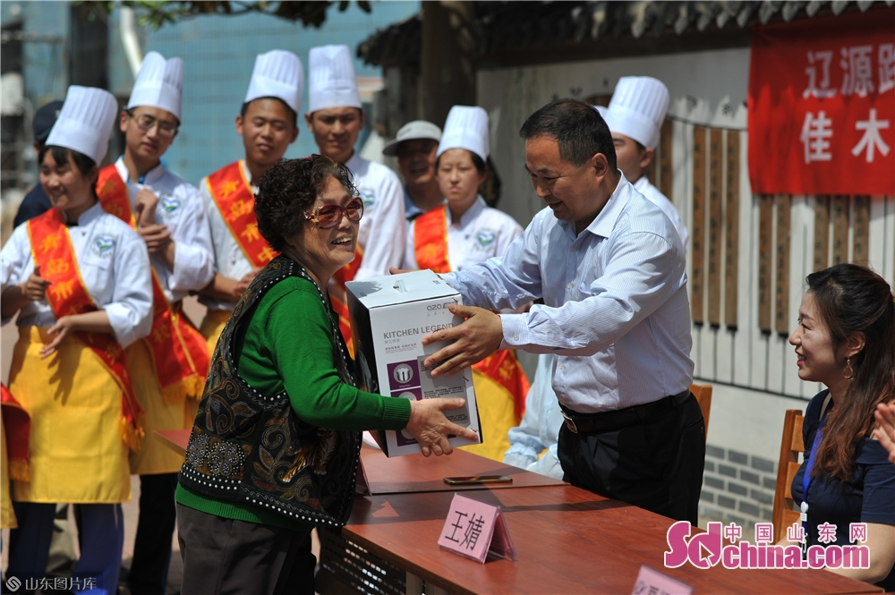 """A community resident receives a prize at the """"Neighbors' Festival"""" in Qingdao, east China's Shandong province, May 28, 2018.<br/>"""