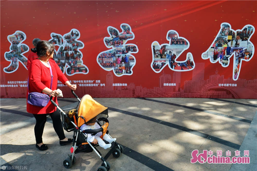 """A community resident walks past the billboard during the """"Neighbors' Festival"""" in Qingdao, east China's Shandong province, May 28, 2018.<br/>"""