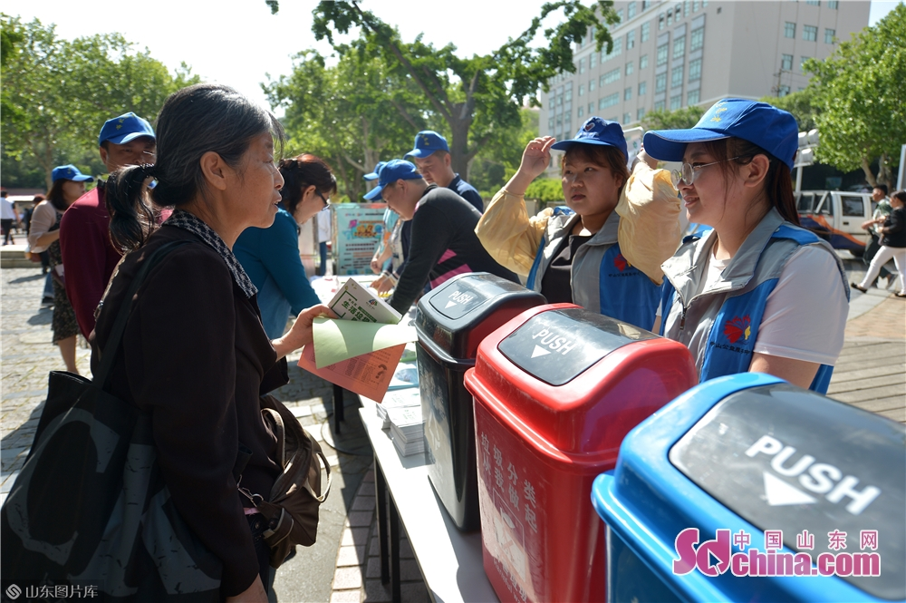 """A community resident asks volunteers for advice on sorting garbage during the """"Neighbors' Festival"""" in Qingdao, east China's Shandong province, May 28, 2018.<br/>"""