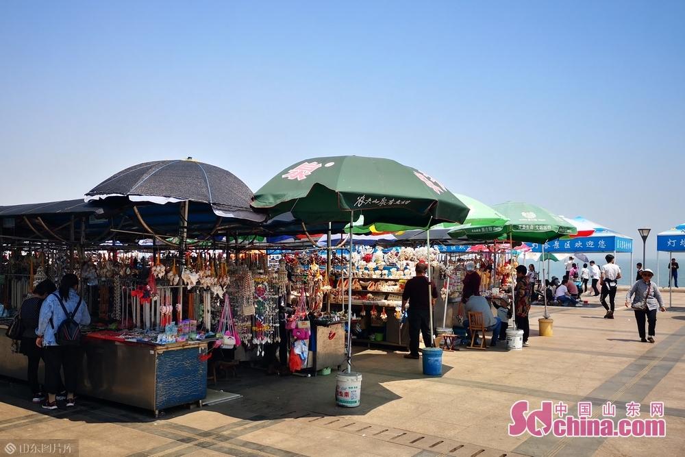 海边摊位上游客在挑选特产。<br/>