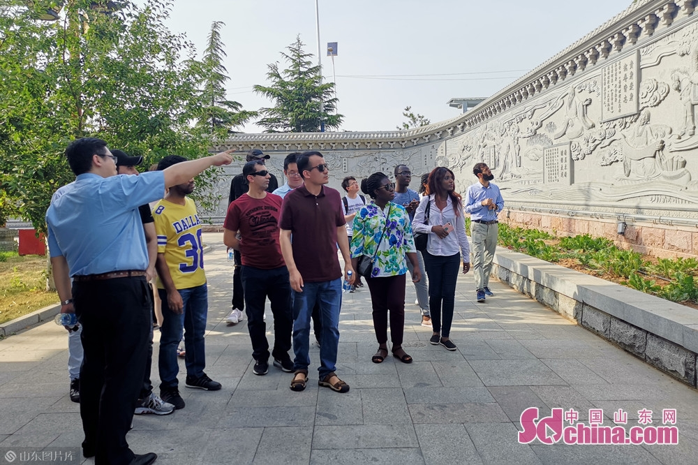 スタッフは外国人に漢方薬文化の彫刻壁を紹介している。<br/>  中国山東網