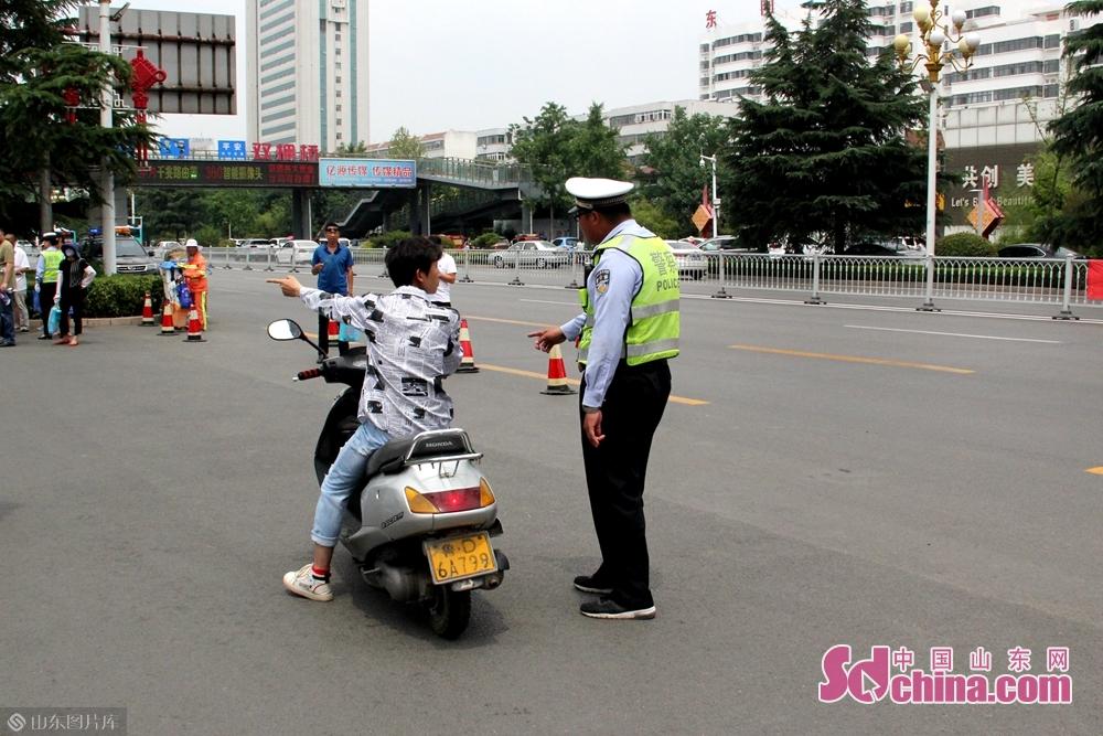 <br/>  考试结束前,交警在校外维持秩序,引导家长在校门两侧等候。一位骑车逆行的小伙子被交警拦下,进行劝导。<br/>