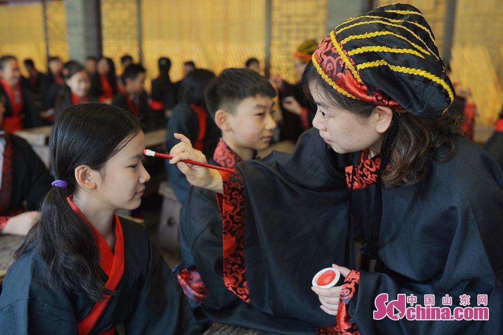<br/>  在青岛市崂山书院举行的&ldquo;成童礼&rdquo;仪式上,老师为毕业生描红&ldquo;朱砂启智&rdquo;。<br/>