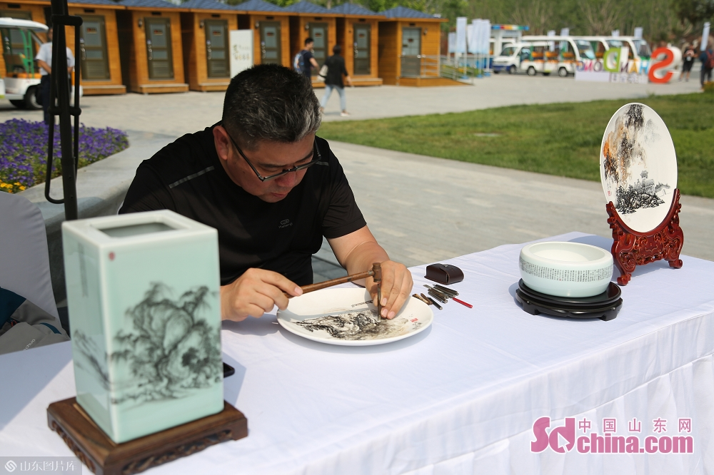 An artist carves on porcelain during the International Horticultural Exhibition in Beijing, capital of China on June 20, 2019. The &ldquo;Shandong Day&rdquo; event kicked off on Thursday.<br/>