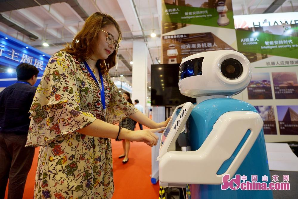 <br/>  6月27日,游客在2019国际虚拟现实创新大会上体验迎宾服务机器人。<br/>