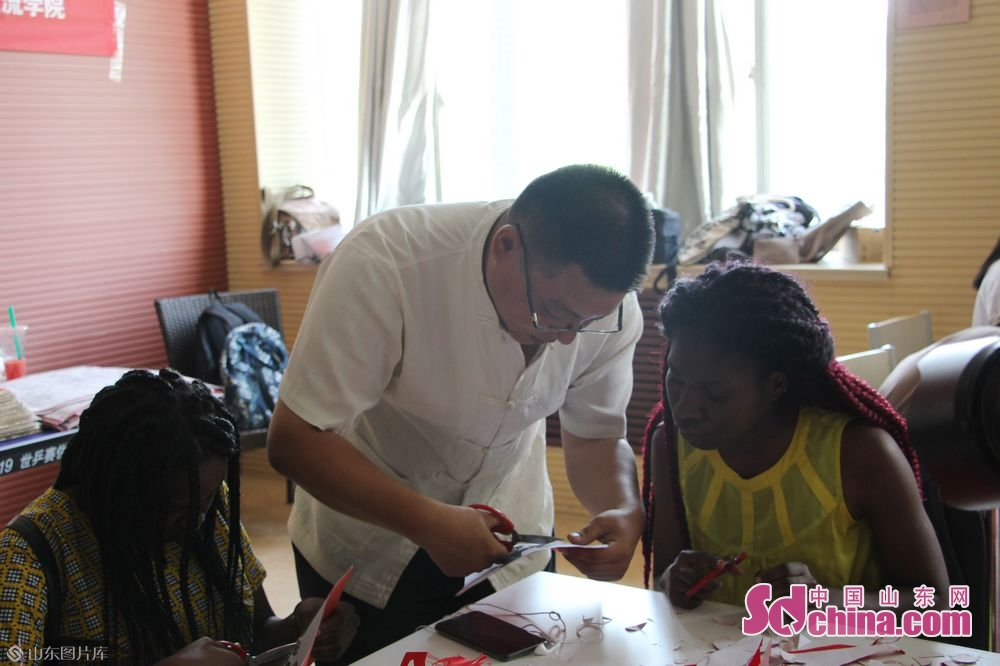 Wang Tao demonstrates how to cut the paper.<br/>